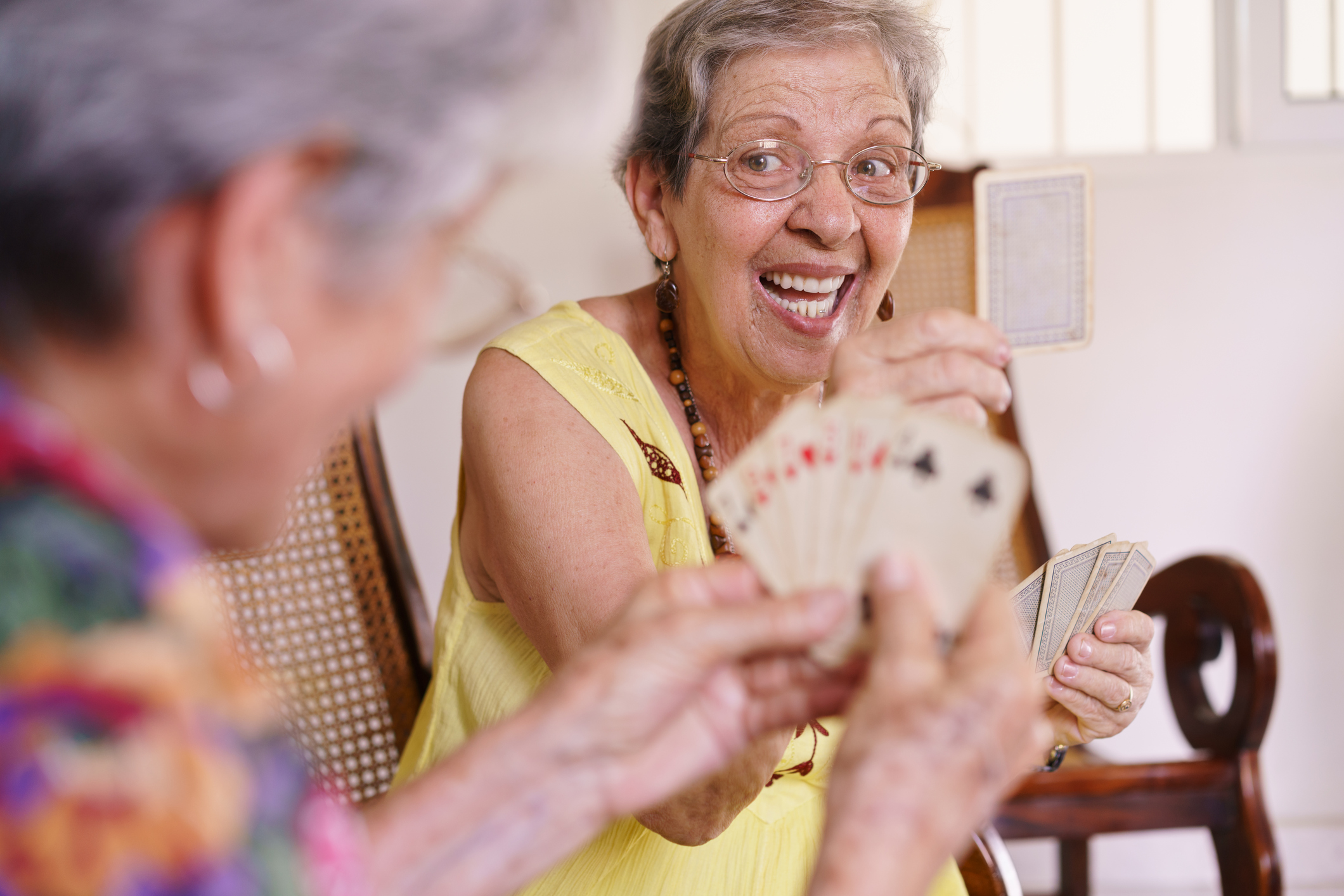 Adult day care benefits seniors by providing socialization opportunities, like these two senior women enjoying a game of cards.
