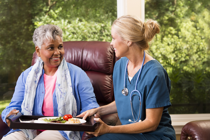 A senior woman speaks to her home health care nurse. As a senior ages, they may find themselves deciding between in-home senior care and assisted living. There are benefits to both, depending on the senior's needs.