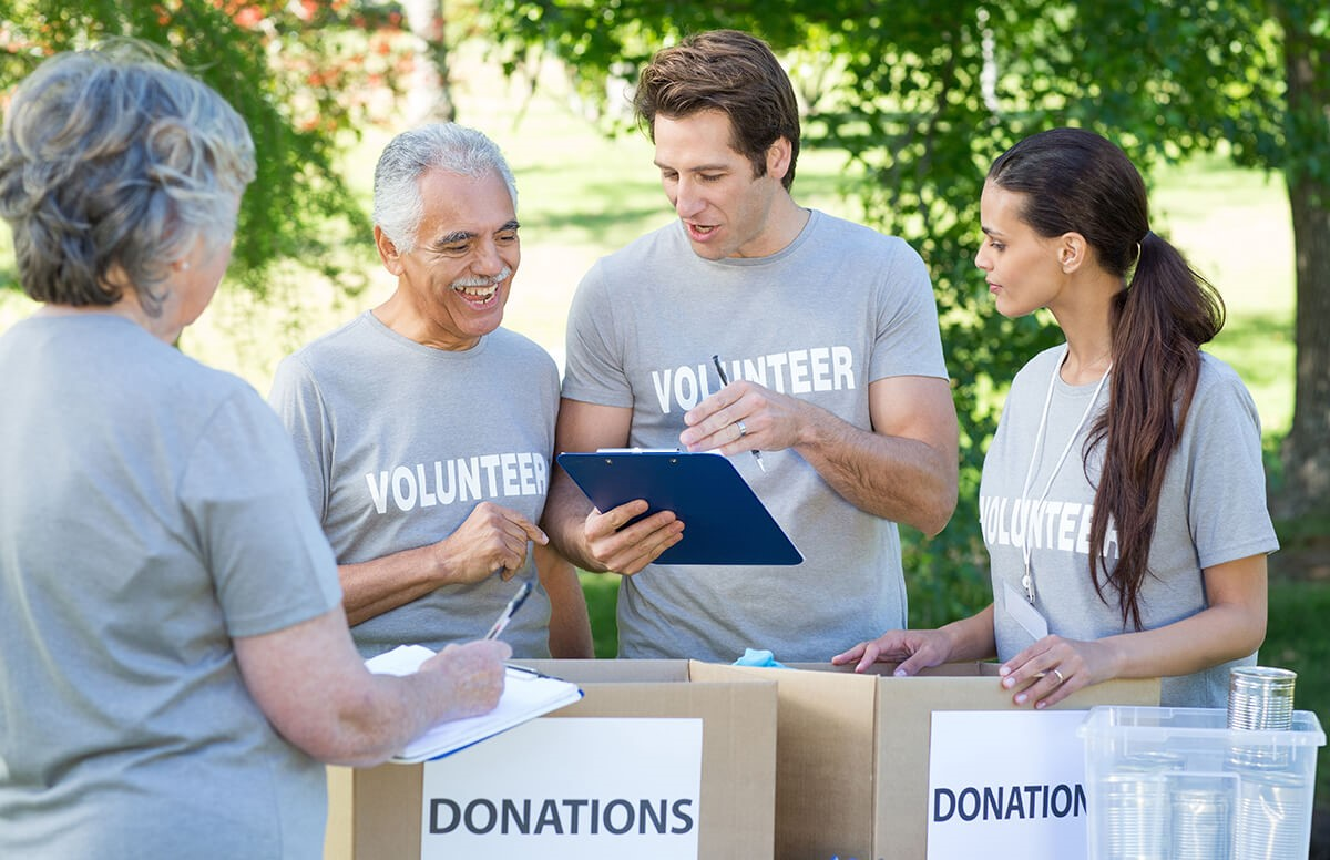 Community involvement is a great way to improve health and happiness in seniors—while benefitting your neighborhood! Here, a group of senior and adult volunteers collect donations.