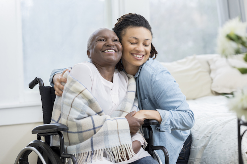 A woman hugs her senior mother to stay positive as a senior caregiver