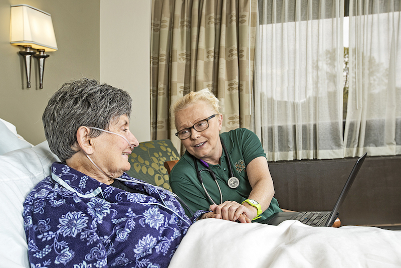 A nurse explains to a senior woman what hospice care does