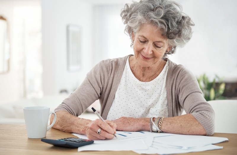 A senior woman reviewing her caregiving schedule, as time management is crucial for a family caregiver.