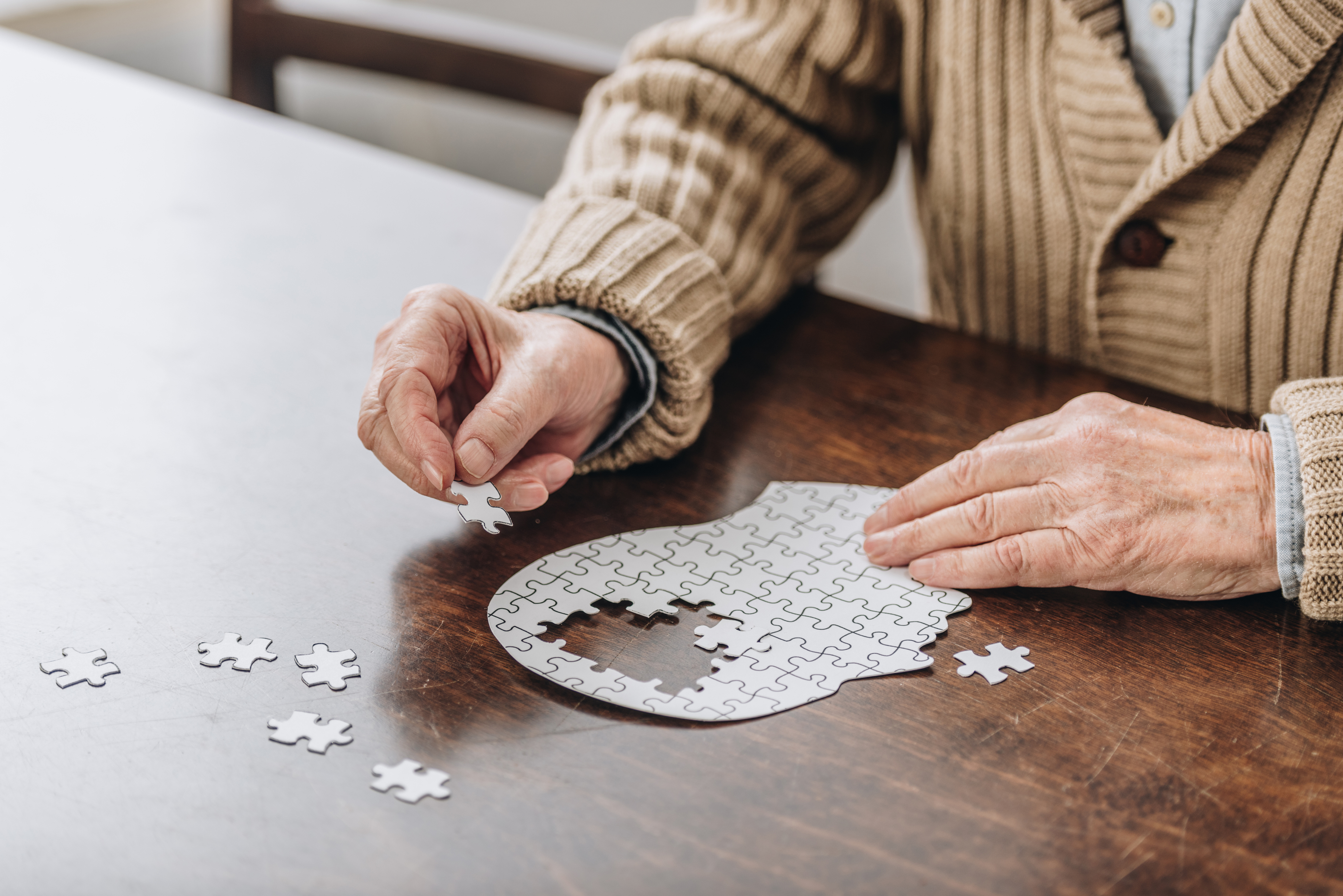 A senior man works on a puzzle, as he knows the importance of brain health
