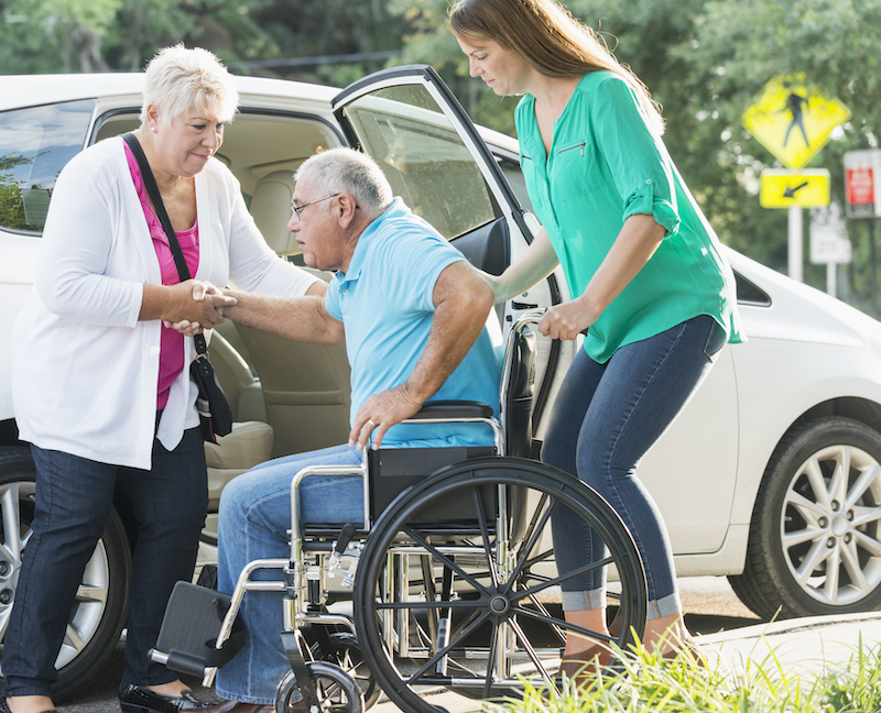 A wife and daughter help a senior man with differing care needs get into a car
