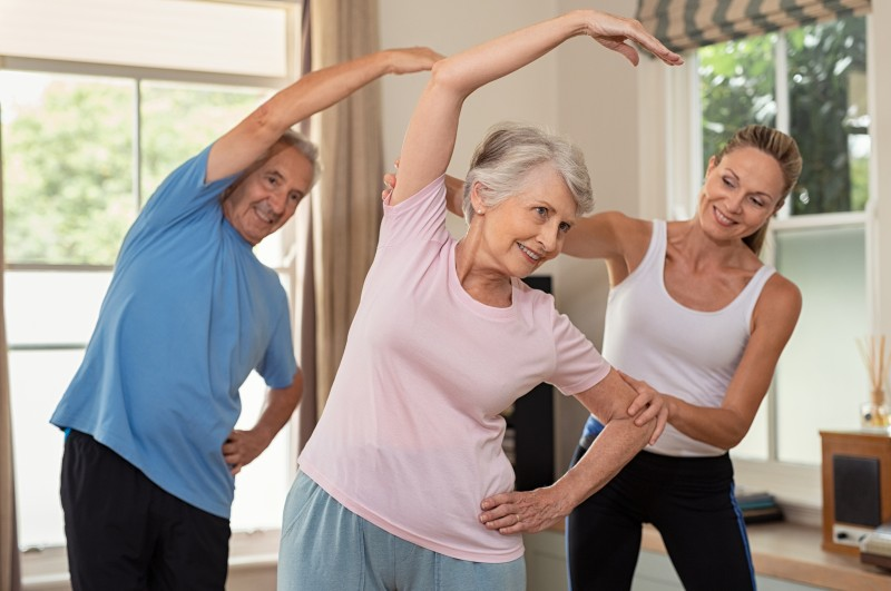 Exercise is just one way of improving quality of life for seniors. Here, a senior man and senior woman work with a trainer in an exercise class.