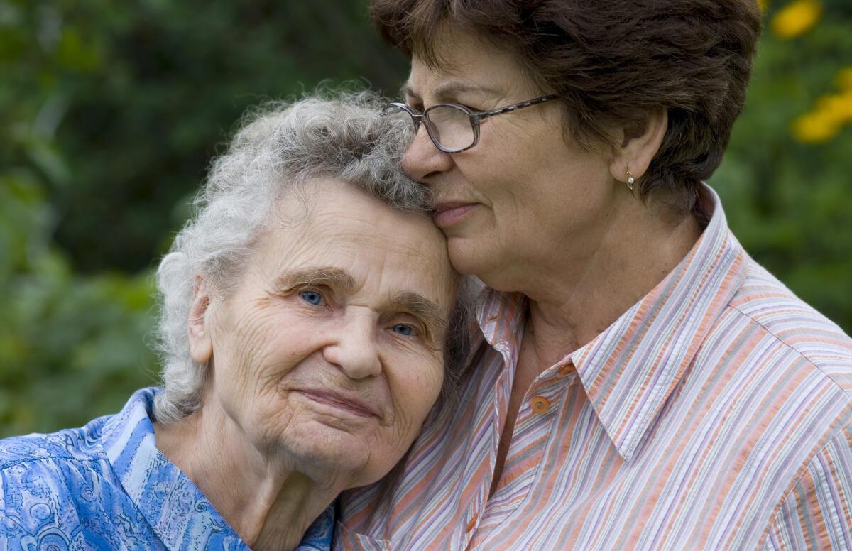 An older adult woman hugs her senior mother.