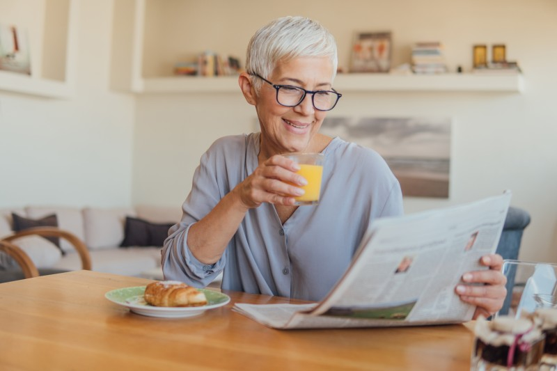 A senior woman enjoys the paper in her home, while she's aging in place.