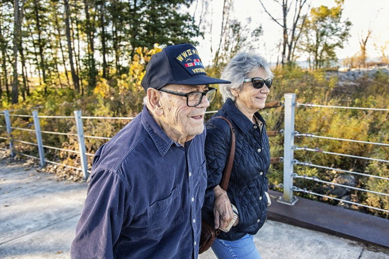 A senior Veteran and his wife walk along a trail at their senior living community.