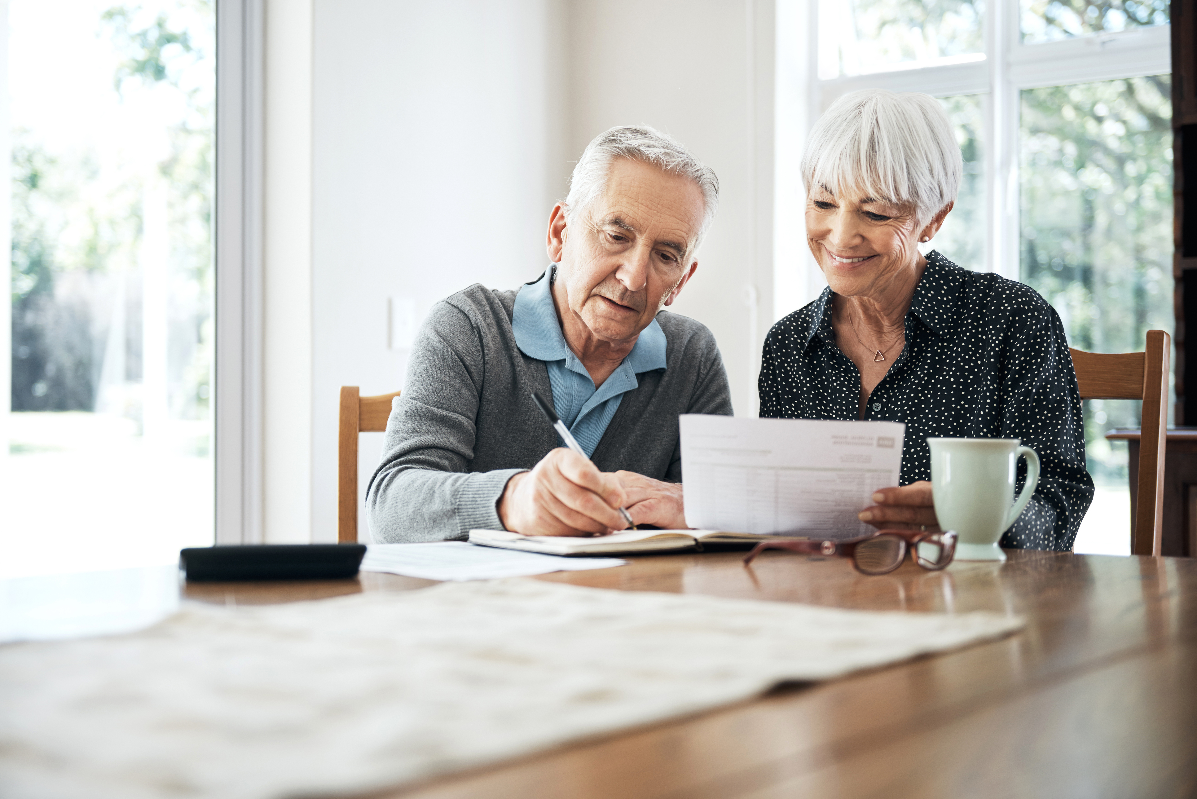 A senior couple reviews their budget and how they save and spend during retirement.