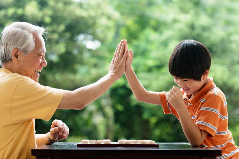 A grandfather and grandson play chess together. Try board games and other activities with your grandchildren.