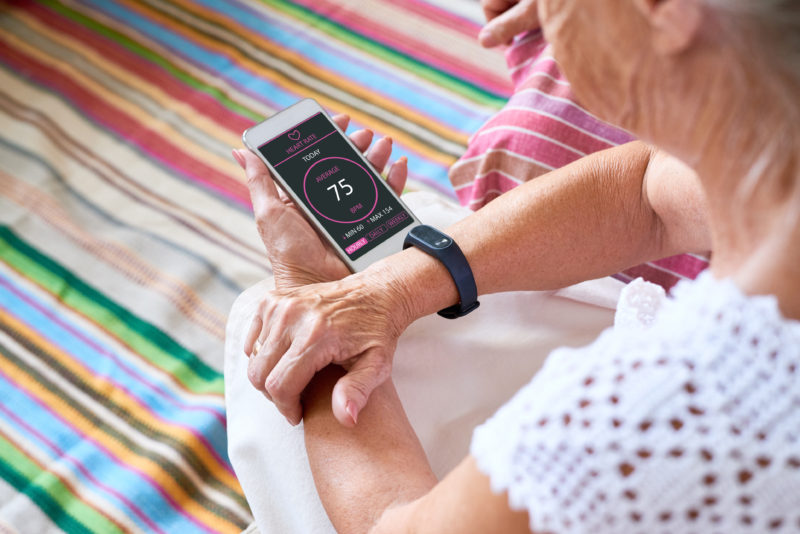 Technology improves quality of life for seniors. Here, a senior woman reviews her heart rate on her smart phone, which is connected to a Fitbit.