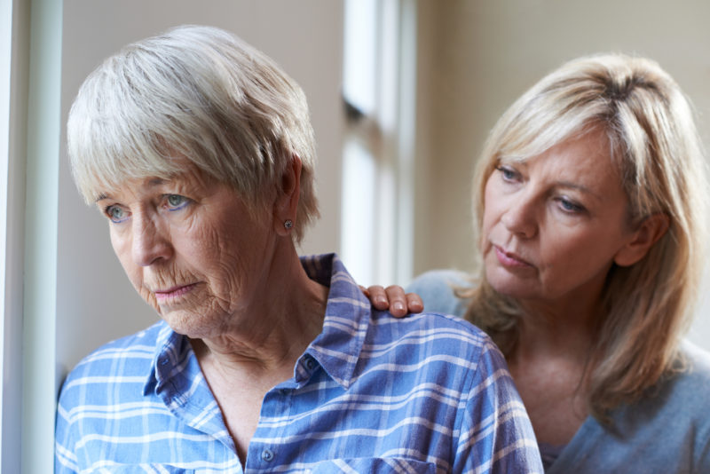 An adult woman talks with her mother as they consider memory care.