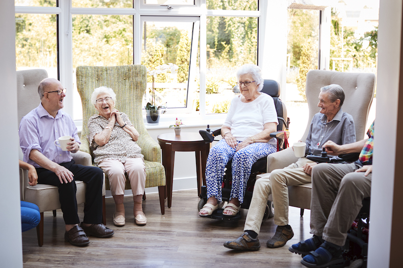 A group of seniors socialize at an independent living community, which offers safety and security to seniors living alone.