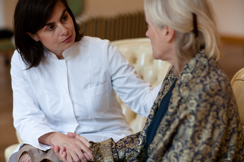 An adult woman cares for her mother, a senior with dementia.