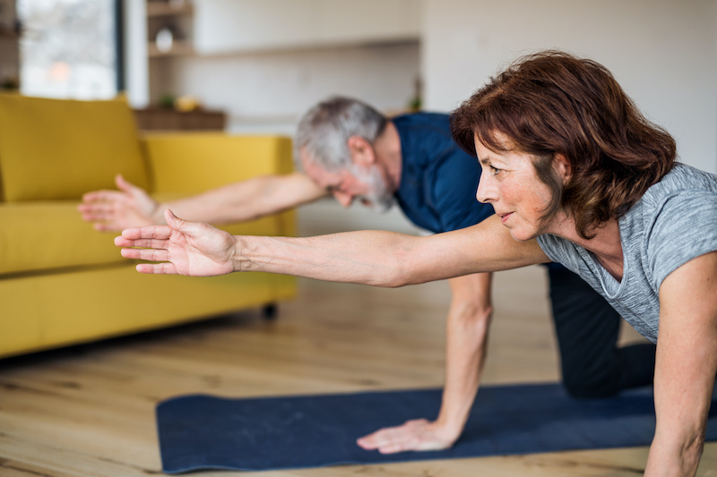 A senior couple stretching for an in-home exercise designed for elderly seniors