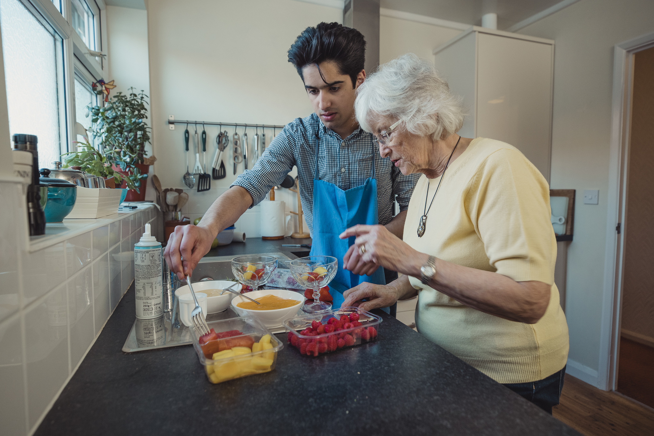 Young man preparing healthy meal with older adult.
