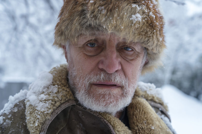 Confused older man looking at camera with fur hat and coat on while wandering with dementia.