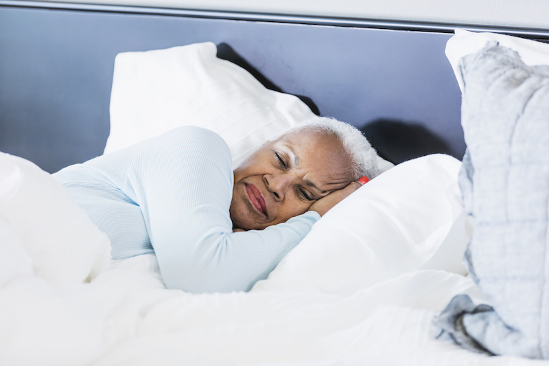 A senior African-American woman sleeping in bed to practice self-care, lying on her side.