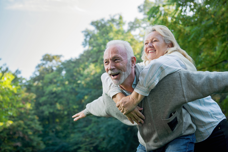 Happy, healthy senior couple smiling outdoors in nature will spring foliage.
