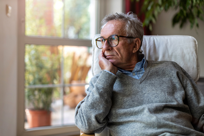 Senior man looking out of window at home coping with senior isolation.