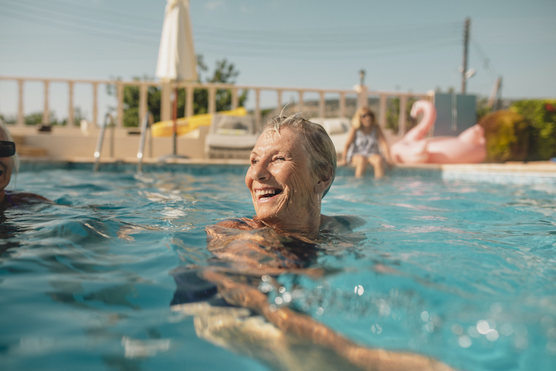 Senior aged woman practicing summer heat safety by swimming in a pool